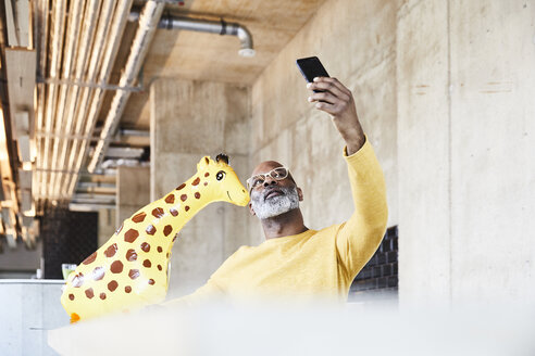 Mature businessman sitting at desk in office with giraffe figurine taking a selfie - FMKF05455