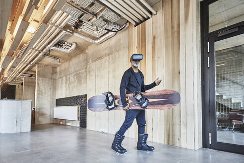 Mature businessman wearing VR glasses holding snowboard in modern office - FMKF05485