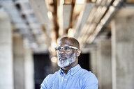 Mature businessman in modern office thinking - FMKF05494