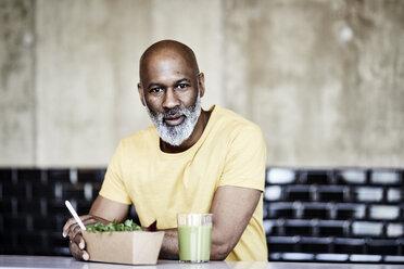 Portrait of mature businessman having lunch break in office - FMKF05503