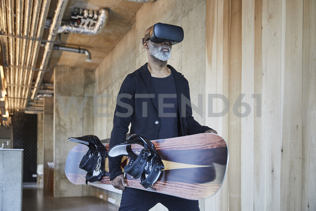 Mature businessman wearing VR glasses holding snowboard in modern office - FMKF05509