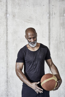 Mature man holding basketball at concrete wall - FMKF05512