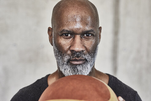 Portrait of serious mature man holding basketball - FMKF05515