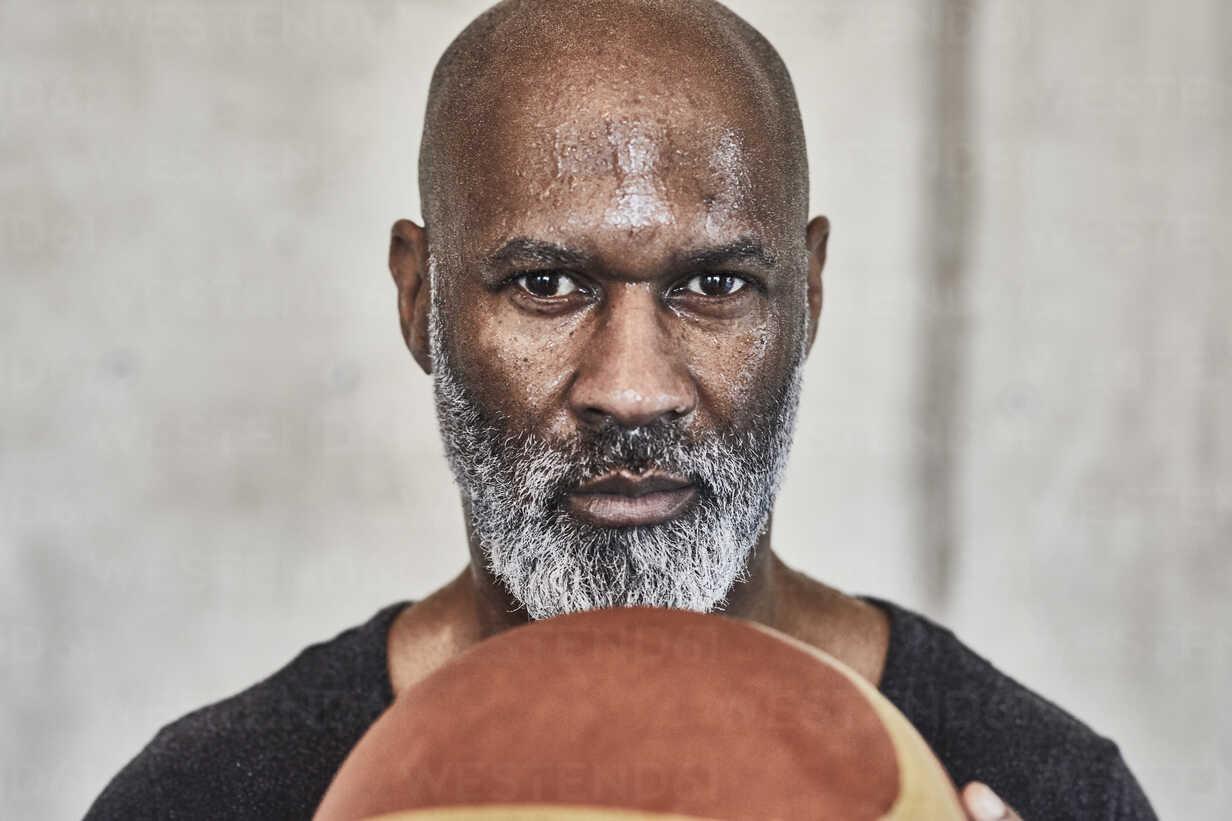 Portrait of serious mature man holding basketball - FMKF05515 - Jo Kirchherr/Westend61