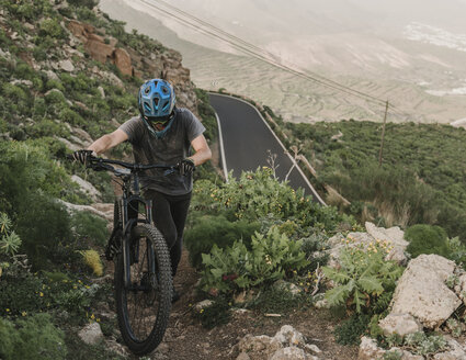 Spain, Lanzarote, mountainbiker pushing his bike on a trail in the mountains - AHSF00098