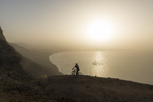 Spain, Lanzarote, mountainbiker on a trip at the coast at sunset enjoying the view - AHSF00104