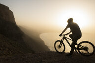 Spain, Lanzarote, mountainbiker on a trip at the coast at sunset enjoying the view - AHSF00107