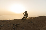 Spain, Lanzarote, mountainbiker on a trip at the coast at sunset - AHSF00110