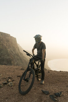 Spain, Lanzarote, mountainbiker on a trip at the coast at sunset - AHSF00113