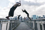 USA, New York, Brooklyn, three young men doing Parkour jumps on pier in front of Manhattan skyline - JUBF00336