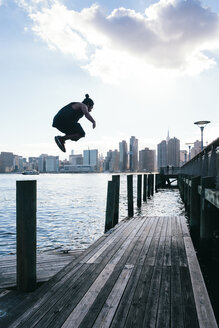 USA, New York, Brooklyn, young man doing Parkour jump from wooden pole in front of Manhattan skyline - JUBF00339