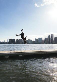 USA, New York, Brooklyn, young man doing backflip on pier in front of Manhattan skyline - JUBF00342