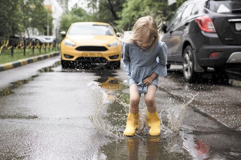 Girl wearing blue dress and rubber boots, jumping in pond on street, yellow car in the background - EYAF00006