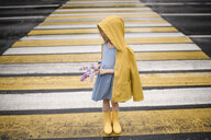 Girl wearing yellow rainjacket, standing on zebra crossing, holding lilac - EYAF00015