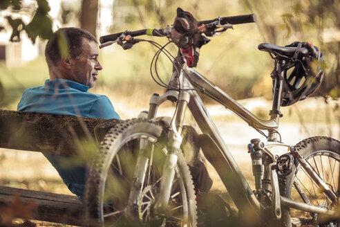 Man with mountainbike having a break sitting on a bench - SEBF00062