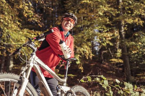 Man with mountainbike having a break in forest - SEBF00071