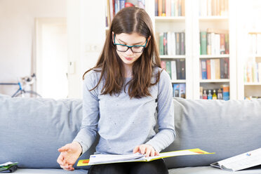 Portrait of girl sitting on the couch at home learning for school - LVF07881