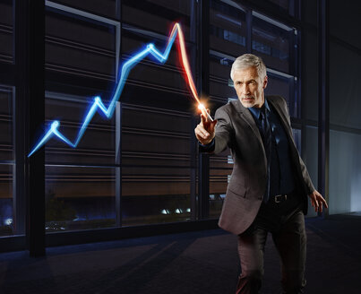 Businessman painting the stock market development with light - RORF01789