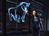 Businesswoman painting a bull with light - RORF01792