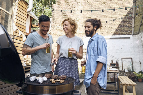 Friends having a barbecue n the backyard, preparing meat on a grill - PDF01817