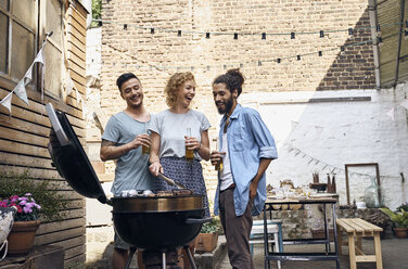 Friends having a barbecue n the backyard, preparing meat on a grill - PDF01823