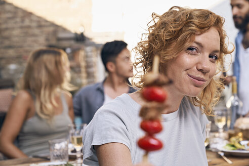 Young woman eating meat skewer at a backyard patry with friends - PDF01856