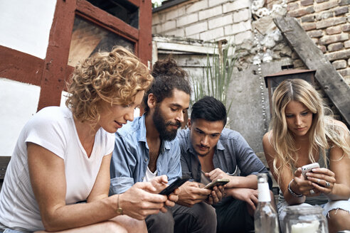 Friends sitting in a backyards, using smartphones - PDF01874