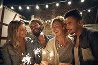 Freinds having a backyard party, burning sparklers - PDF01886