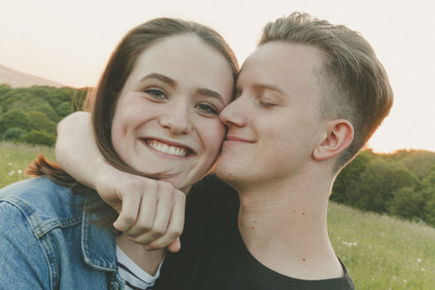 Portrait of happy teenage girl with boyfriend in nature in the evening - ANHF00095