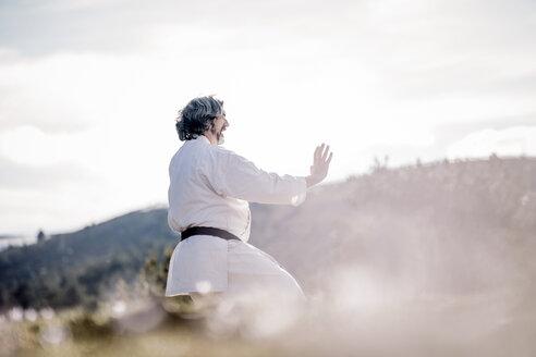Senior man practicing karate outdoors - OCMF00305
