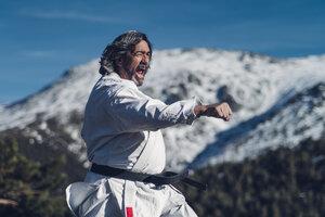 Senior man practicing karate outdoors - OCMF00314