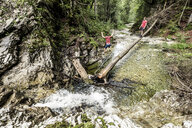 Germany, Bavaria, Upper Bavaria, lake Walchen, two young men are crossing a torrent on a tree trunk, twins - WFF00054
