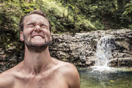 Germany, Upper Bavaria, Bavarian Prealps, lake Walchen, young man is making a face in a cold torrent - WFF00060