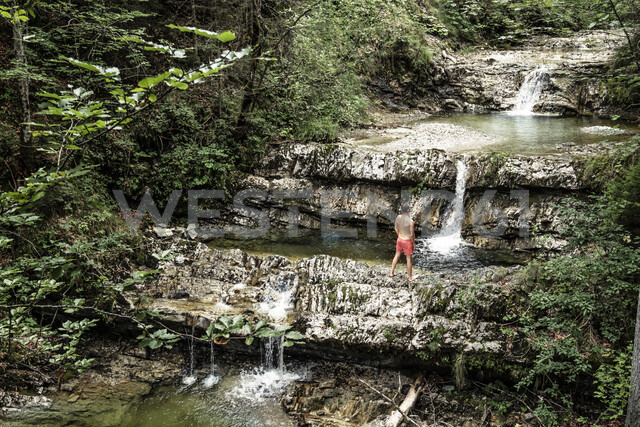 Germany, Upper Bavaria, Bavarian Prealps, lake Walchen, young man is standing in a torrent - WFF00069 - Wilfried Feder/Westend61