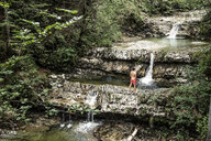 Germany, Upper Bavaria, Bavarian Prealps, lake Walchen, young man is standing in a torrent - WFF00069