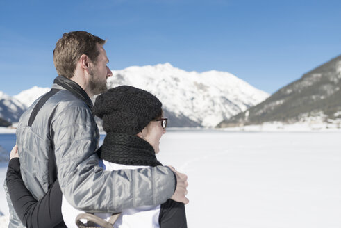 Austria, Tyrol, Achensee, couple looking at frozen lake in winter - MKFF00454