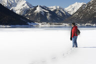 Austria, Tyrol, Achensee, smiling woman standing at frozen lake in winter - MKFF00457