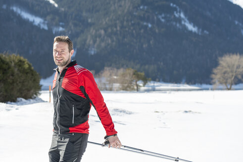 Austria, Tyrol, Achensee, portrait of smiling man doing cross country skiing - MKFF00463