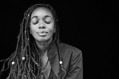 Portrait of woman with dreadlocks in front of black background - FMKF05520
