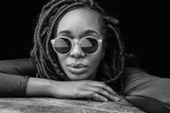 Portrait of woman with dreadlocks wearing sunglasses in front of black background - FMKF05526