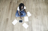 Woman sitting on the floor with digital tablet and blank sheets of paper - FMKF05535