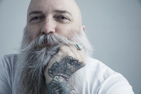 Close up portrait confident Caucasian male hipster with gray beard and tattooed hand on chin - HEROF29972