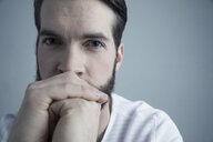 Close up portrait confident brunette Caucasian young man with hands clasped covering mouth - HEROF29975