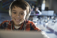 Close up smiling pre-adolescent boy wearing headphones listening to music at laptop - HEROF29996