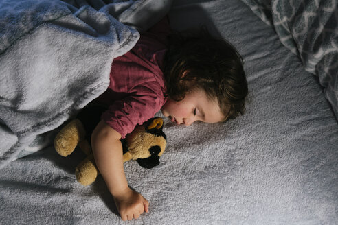 Toddler girl sleeping in bed with a soft toy dog - GEMF02911
