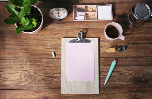 Clip board with blank pink paper, coffee mug and other utensils on desk at home office, top view - MOMF00637