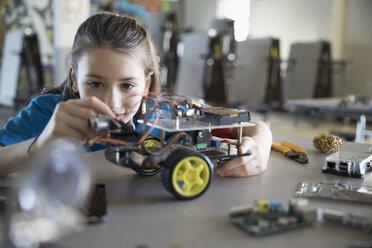 Pre-adolescent girl assembling robotics in classroom - HEROF30059