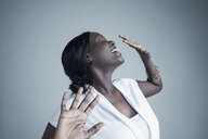 Portrait playful African American young woman smiling and dancing with eyes closed and head back - HEROF30073