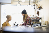 Hipster barista with long beard helping teenage girl with shaved head in cafe - HEROF30123