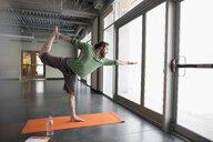 Man practicing yoga king dancer pose on yoga mat in gym studio - HEROF30126